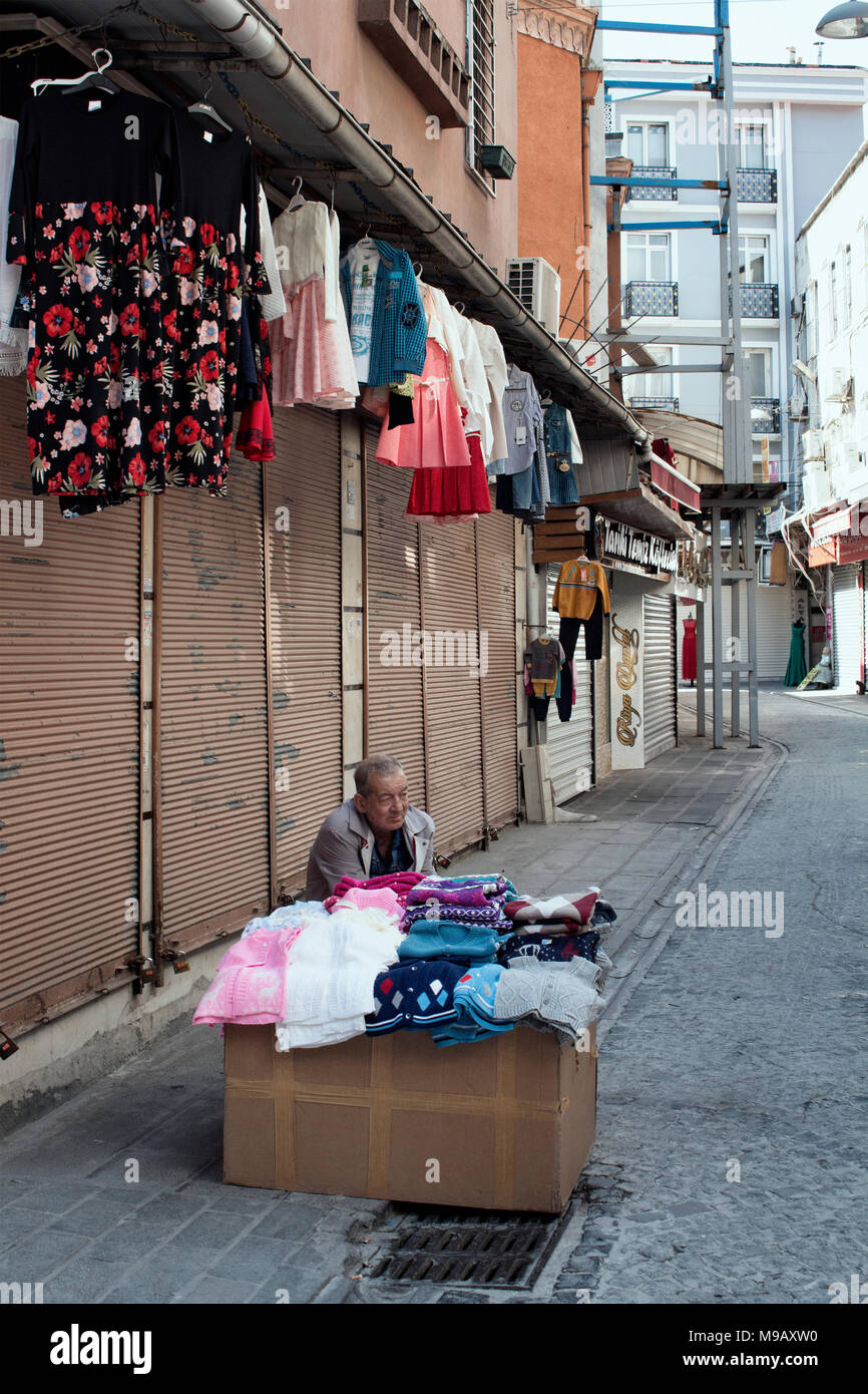 Old, street seller wait for customers in Eminonu / Sirkeci area of Istanbul. - Stock Image