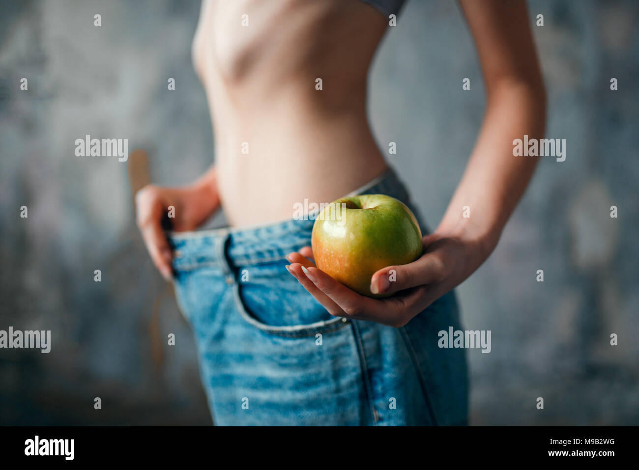Woman with apple in hand tries on big size jeans - Stock Image