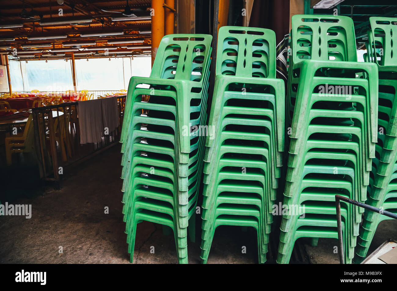 Chairs piled up in closed restaurant at Lamma island village in HongKong - Stock Image