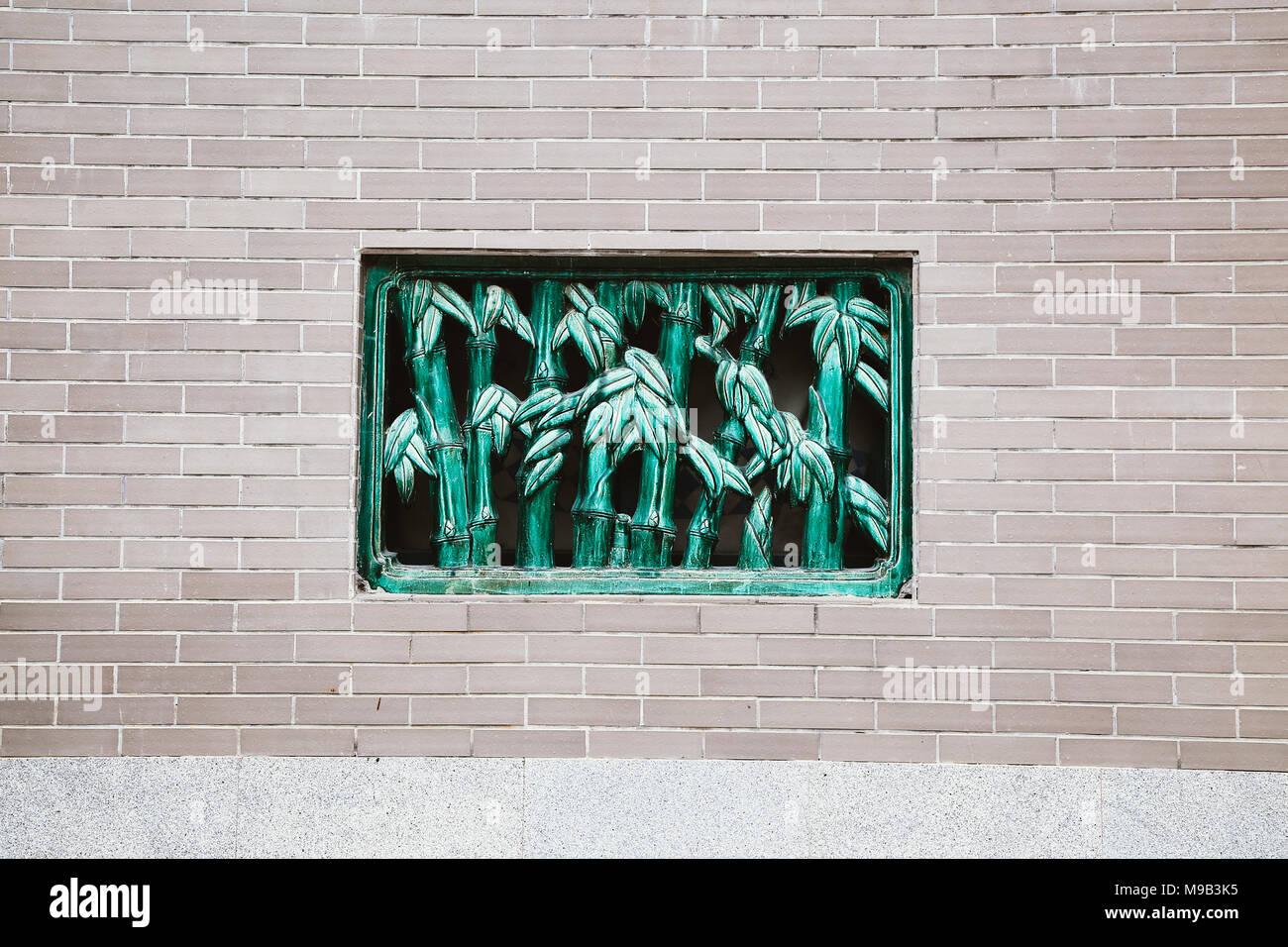 Chinese brick wall and bamboo style window - Stock Image