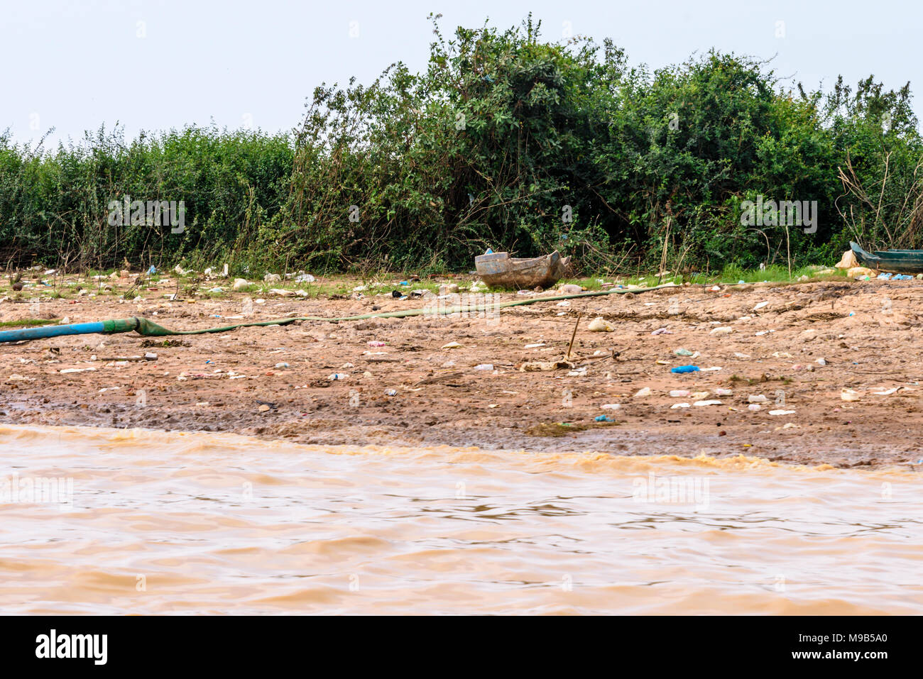 Huge amounts of plastic bottles, bags and boxes line the Siem Reap river in Cambodia. - Stock Image