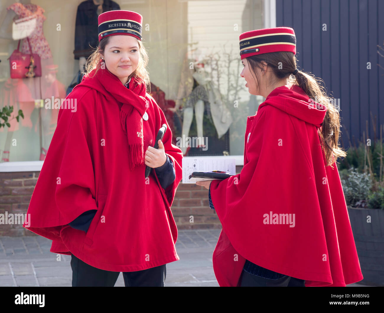 Young female guides at Bicester Village Outlet Shopping Centre, Bicester, Oxfordshire, England, United Kingdom - Stock Image