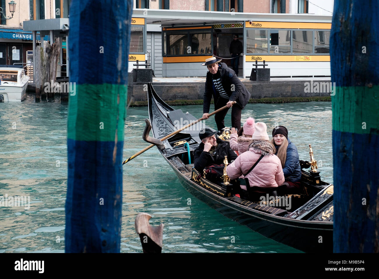 A gondolier guides a gondola across the Grand Canal at Rialto Bridge on a pleasant day in March. Venice, Italy - Stock Image