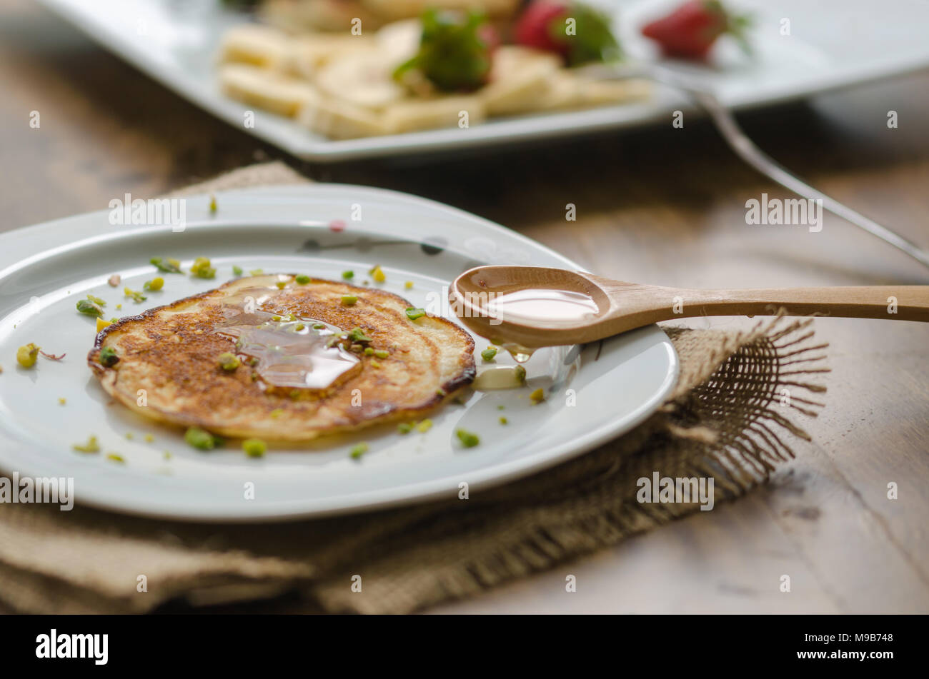 Stack of Turkish -style pancakes with pistachio and honey - Stock Image
