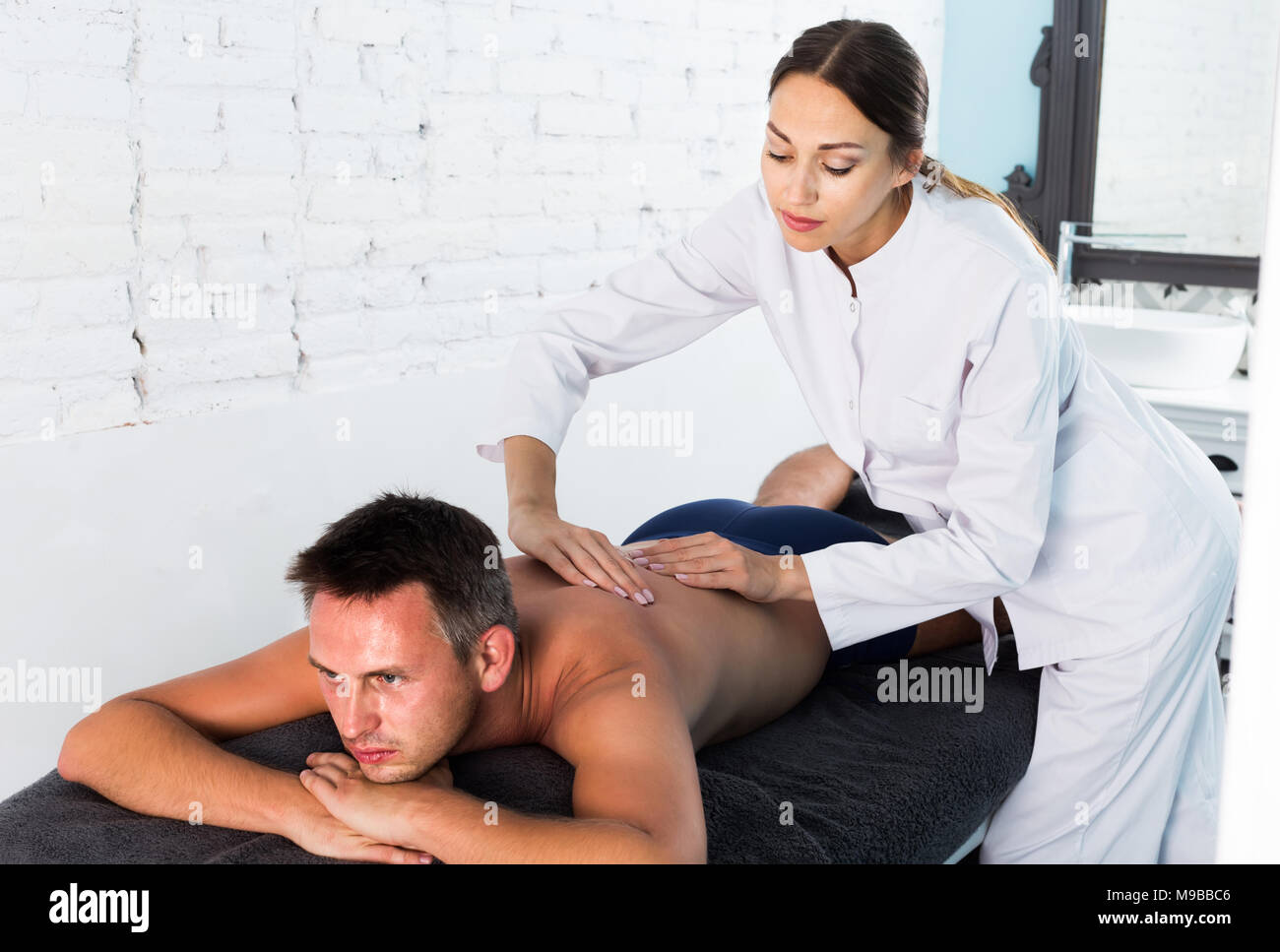 Professional masseuse performing back massage to positive swedish male client in spa center Stock Photo