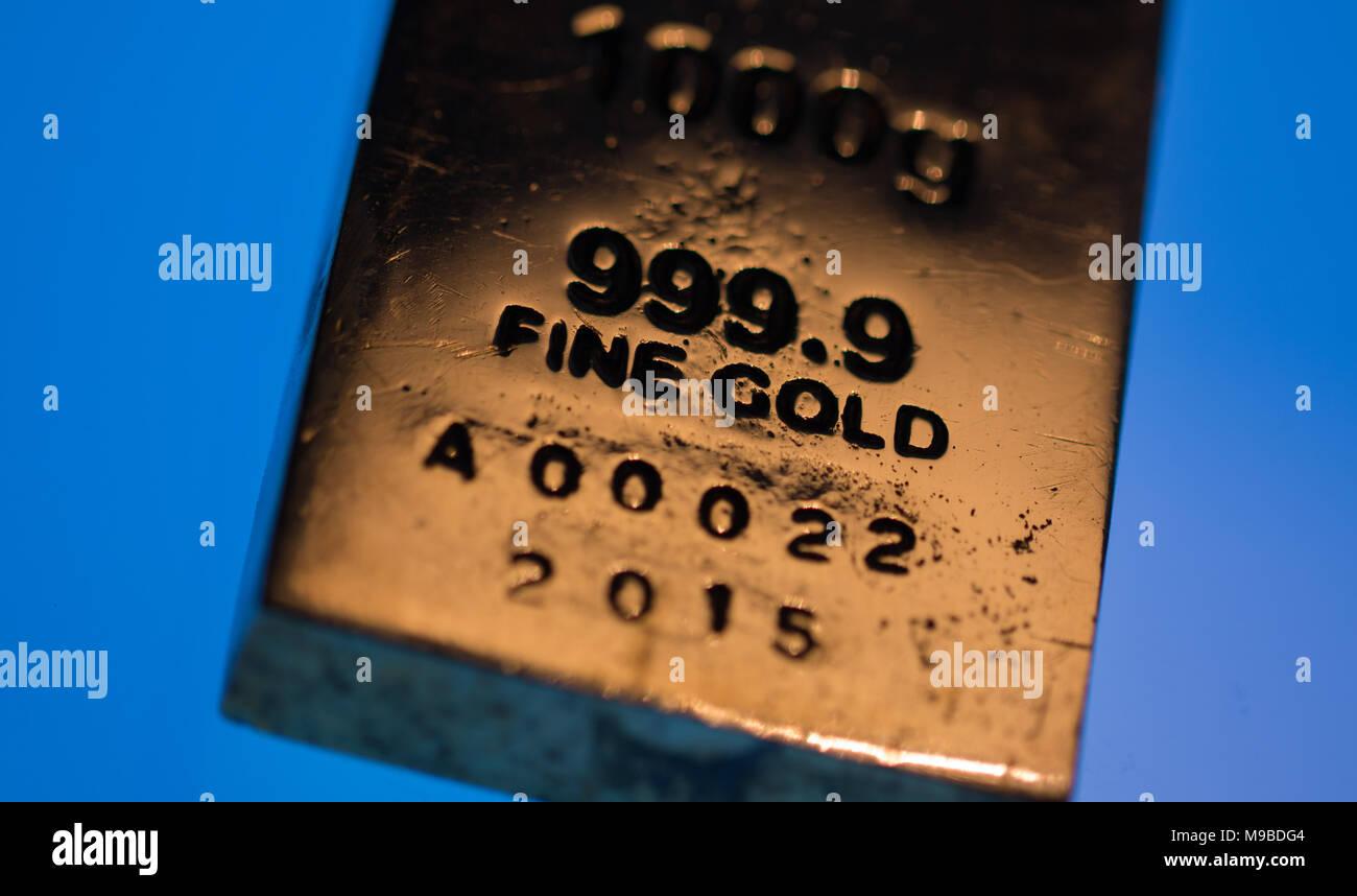 Gold Bar detail set against bright blue background, studio shot - Stock Image
