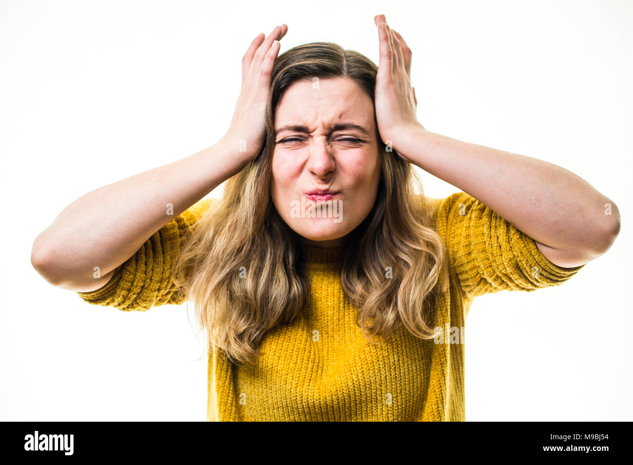 A young Caucasian woman girl pressing the palms of her hands against her head, suffering headache head pain migraine , against a white background, UK - Stock Image