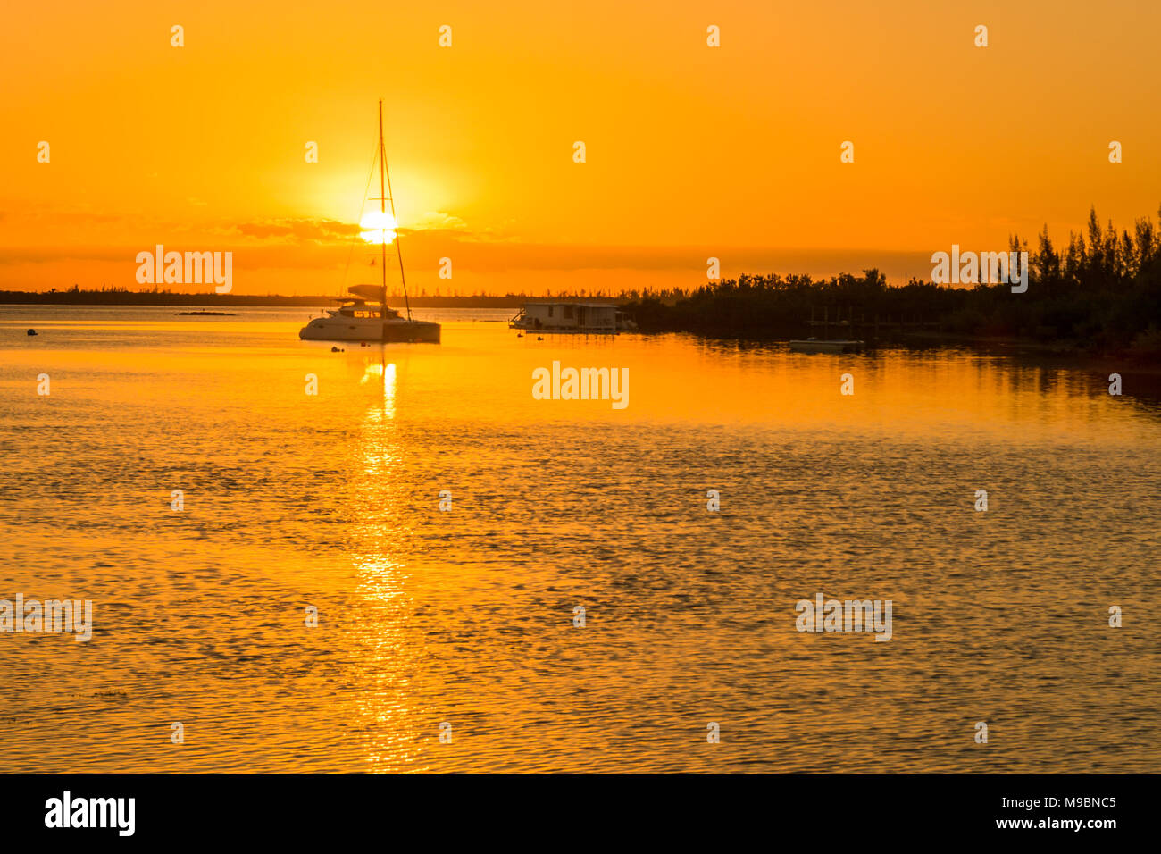 Bahamian Sunrise over gorgeous ocean showing catamaran sailboat and coastal line - Stock Image