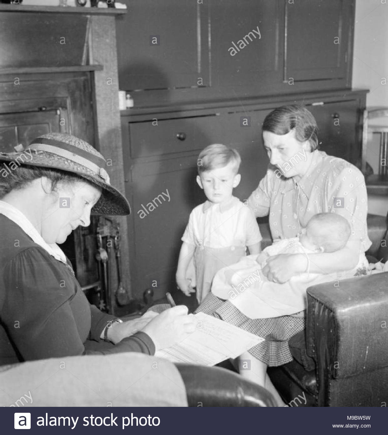 Local Government in a Country Town- Everyday Life in Wotton-under-edge, Gloucestershire, England, UK, 1944 Health Visitor Miss Sumption Jones (left) calls on Mrs C S Hayward and her two children, Timothy (aged 2 and a half) and Miriam (aged 4 months) at their home in Wotton-under-Edge in Gloucestershire. The original caption explains that the Health Visitor's visits begin when a child is 14 days old. - Stock Image