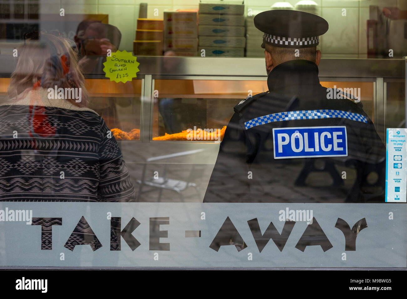 A police officer on the beat in uniform resting and eating lunch. Policeman in a takeaway food outlet. Bobby on the beat policing in the community. - Stock Image