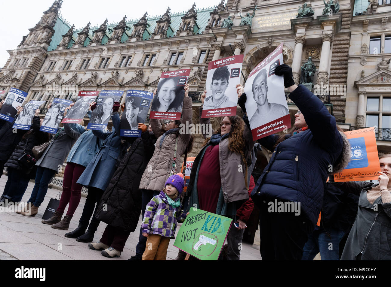 """24 March 2018, Germany, Hamburg: Americans and Germans protesting with pictures of people killed during school shootings in the US in front of City Hall during the """"March for our Lives"""" for stricter gun control in the US. Photo: Markus Scholz/dpa Stock Photo"""