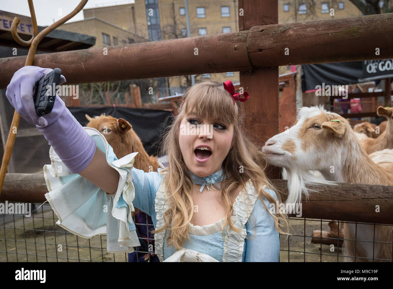 London, UK. 24th March, 2018. Little Bo-Peep takes selfie photos with some of the contenders just before the main race at The 10th Annual Oxford vs Cambridge Goat Race, Spitalfields City Farm. Credit: Guy Corbishley/Alamy Live News - Stock Image