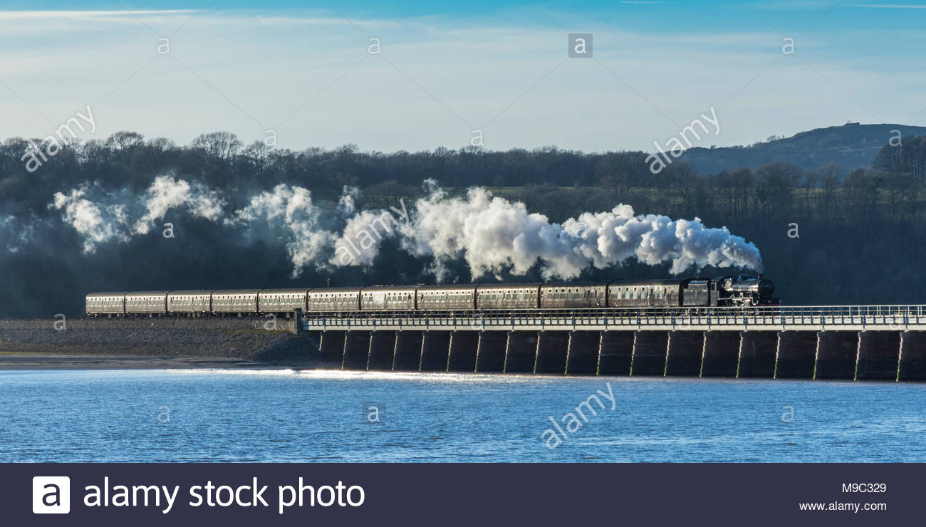 Arnside, Cumbria, UK, 24 March 2018, the setting sun illuminates 45690, 'Leander' locomotive, pulling the Cumbrian Coast Express Steam Tour as it crosses the Kent Viaduct at Arnside. The viaduct over the River Kent at the head of Morecambe Bay is  552 yards (505 m) long, with 50 piers. It was built in 1857 and rebuilt in 1915. Credit: Keith Douglas News/Alamy Live News - Stock Image