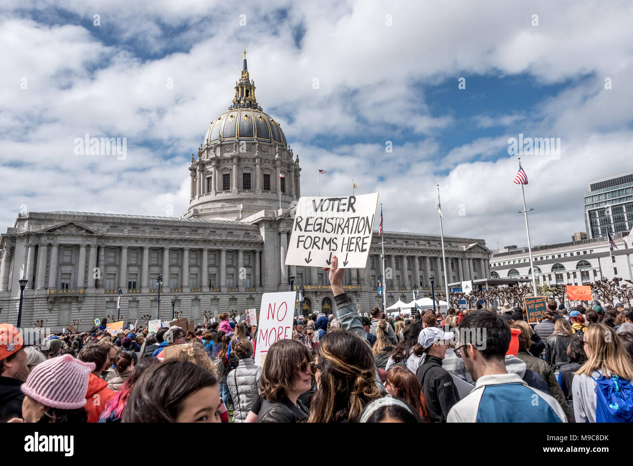 San Francisco, USA. 24th March, 2018. March for Our Lives rally and march to call for gun control and end gun violence; amid the crowd a sign reads 'Voter registration forms here' with arrows. Mobilizing new, young voters is a common theme in the student-led movement. Shelly Rivoli/Alamy Live News - Stock Image
