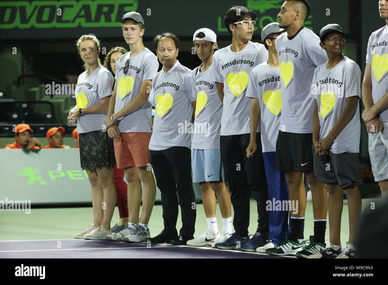KEY BISCAYNE, FL - MARCH 24: Angelique Menses of Marjory Stoneman Douglas High School stands with Tournament director James Blake after singing the National Anthem with members of the boys and girls tennis team and the players from the ATP and WTA including Nick Kyrgios and  during Day 6 of the Miami Open at the Crandon Park Tennis Center on March 24, 2018 in Key Biscayne, Florida.    People:  Atmosphere - Stock Image