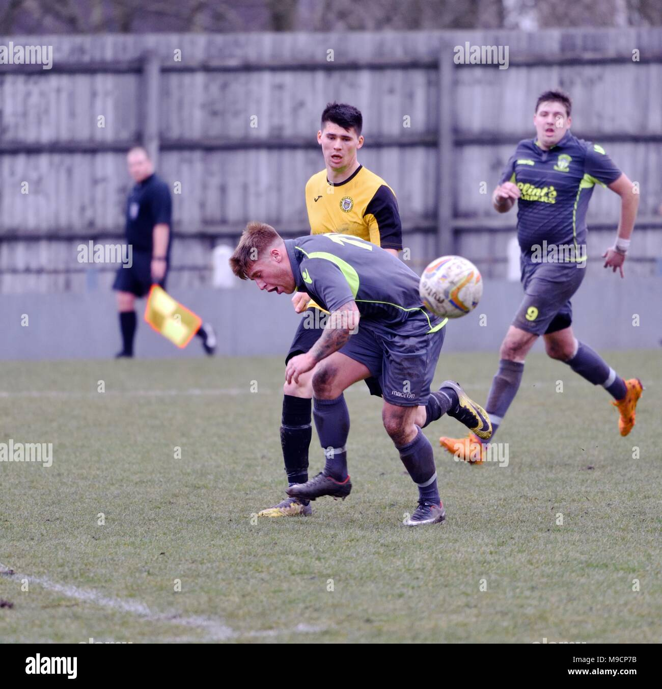 Action from the semi-professional football match between New Mills and Abbey Hulton United in the North-West Football League. - Stock Image
