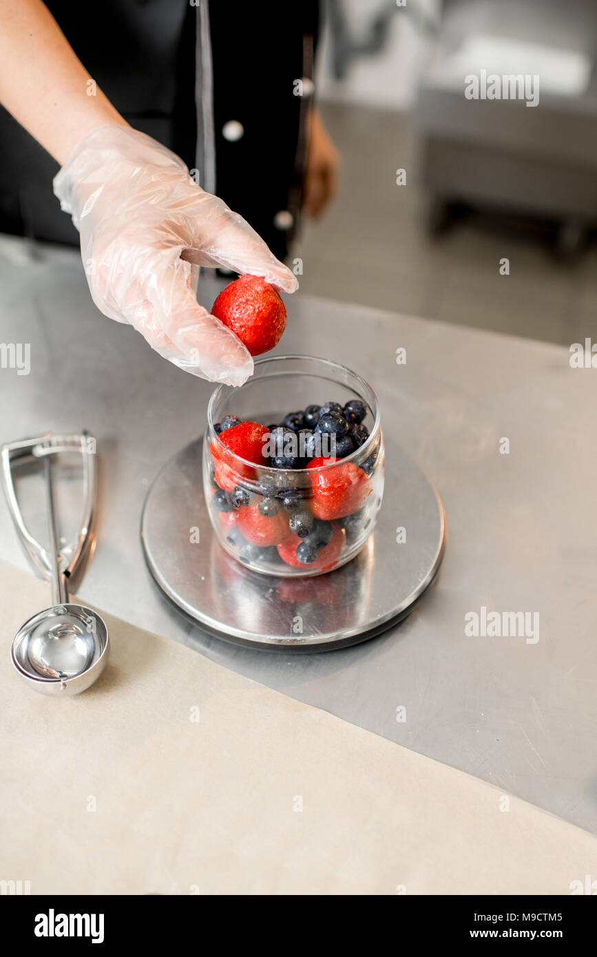 Weighting berries for ice cream production - Stock Image