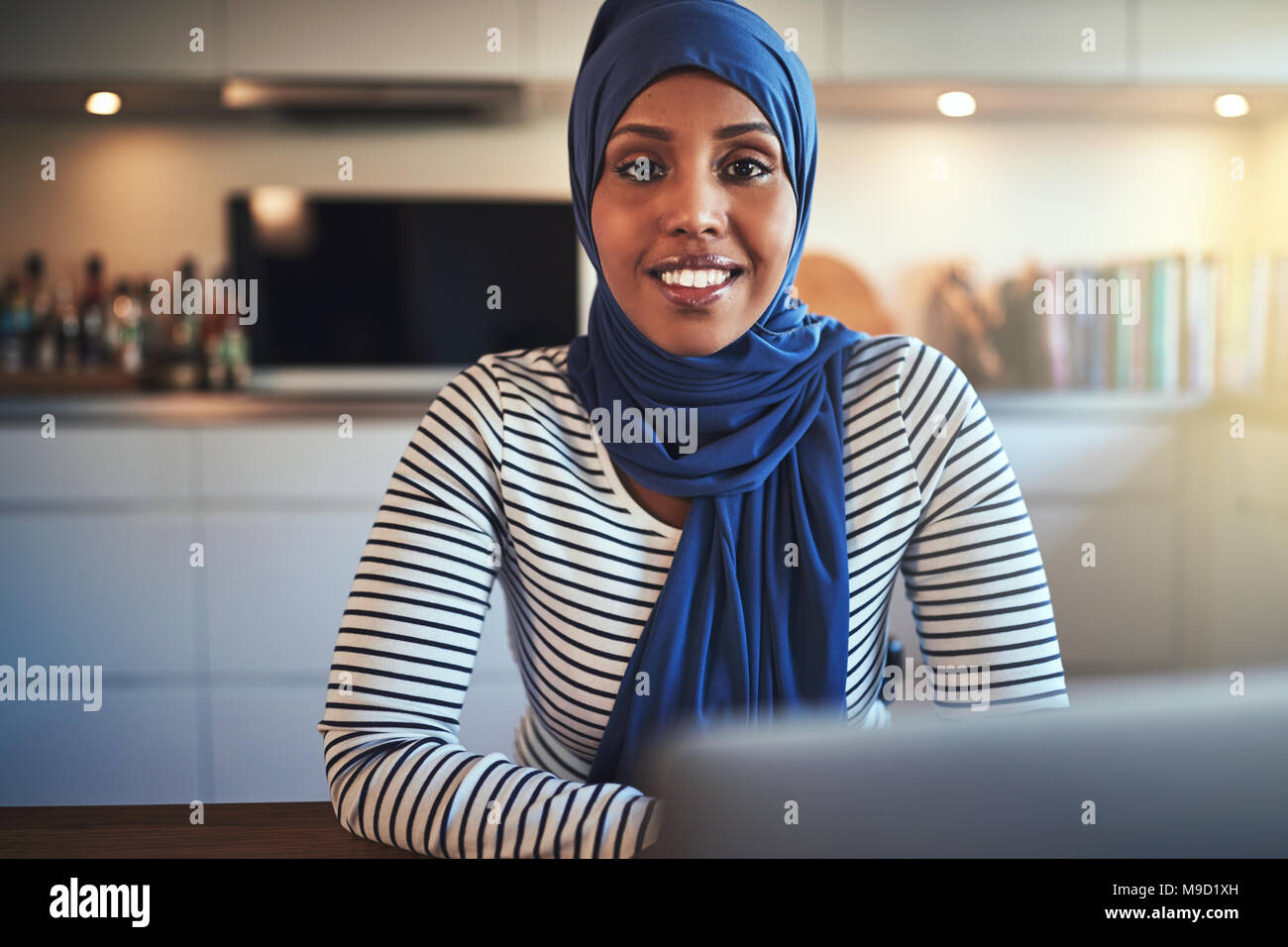Smiling young Muslim female entrepreneur wearing a hijab working on a laptop while sitting at a table in her kitchen Stock Photo