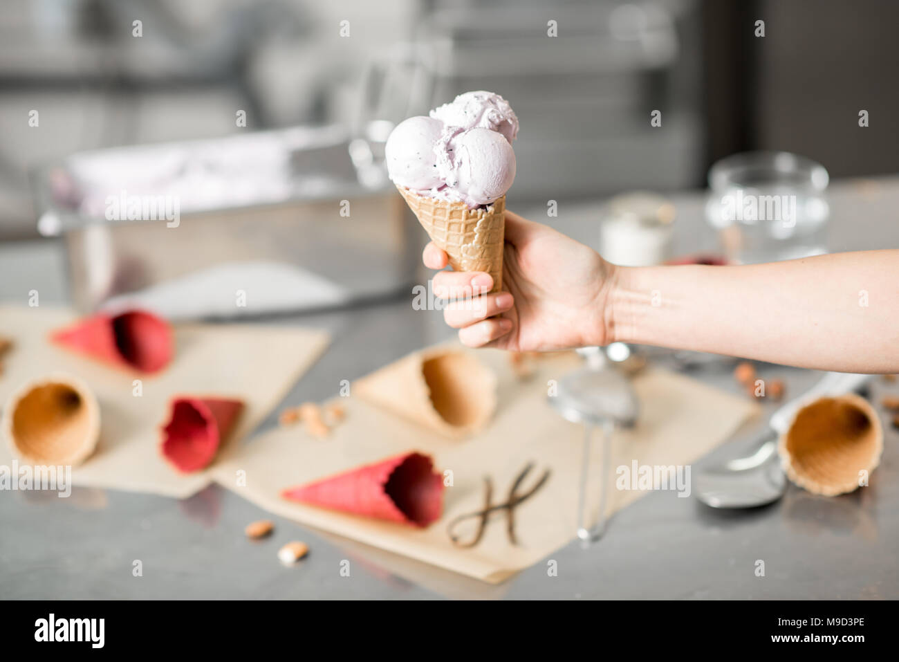 Holding waffle cone with ice cream indoors Stock Photo