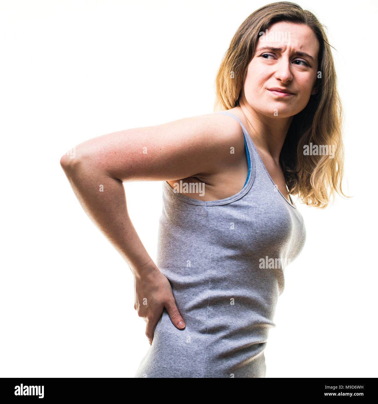 A young Caucasian woman girl wearing a grey vest, suffering from lower back pain, rubbing her back, standing against a white background, UK - Stock Image