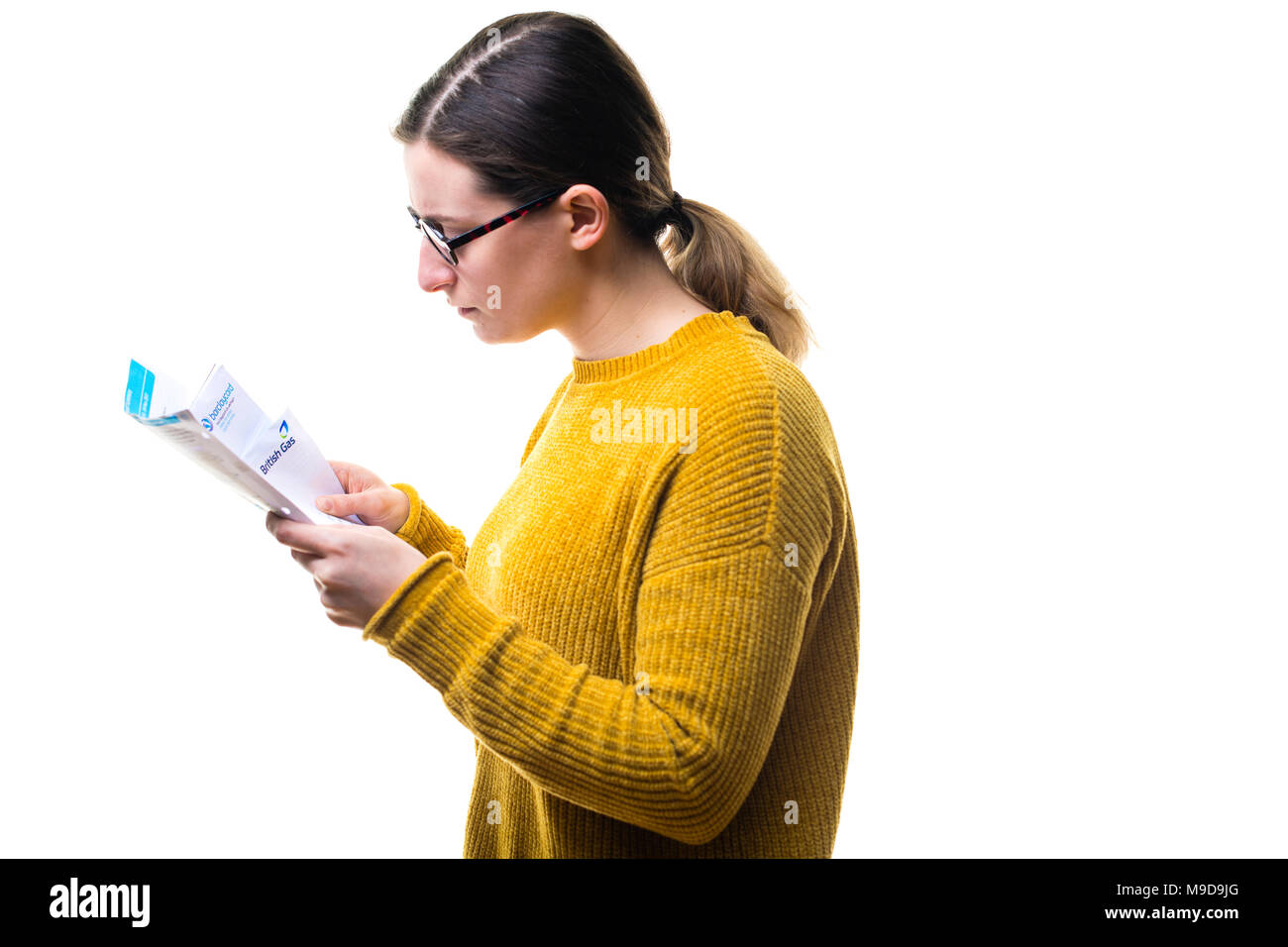 Money Worries and personal finances : A young Caucasian woman girl wearing a yellow jumper sweater, looking at her bills and worried about paying domestic utility power charges , UK - Stock Image