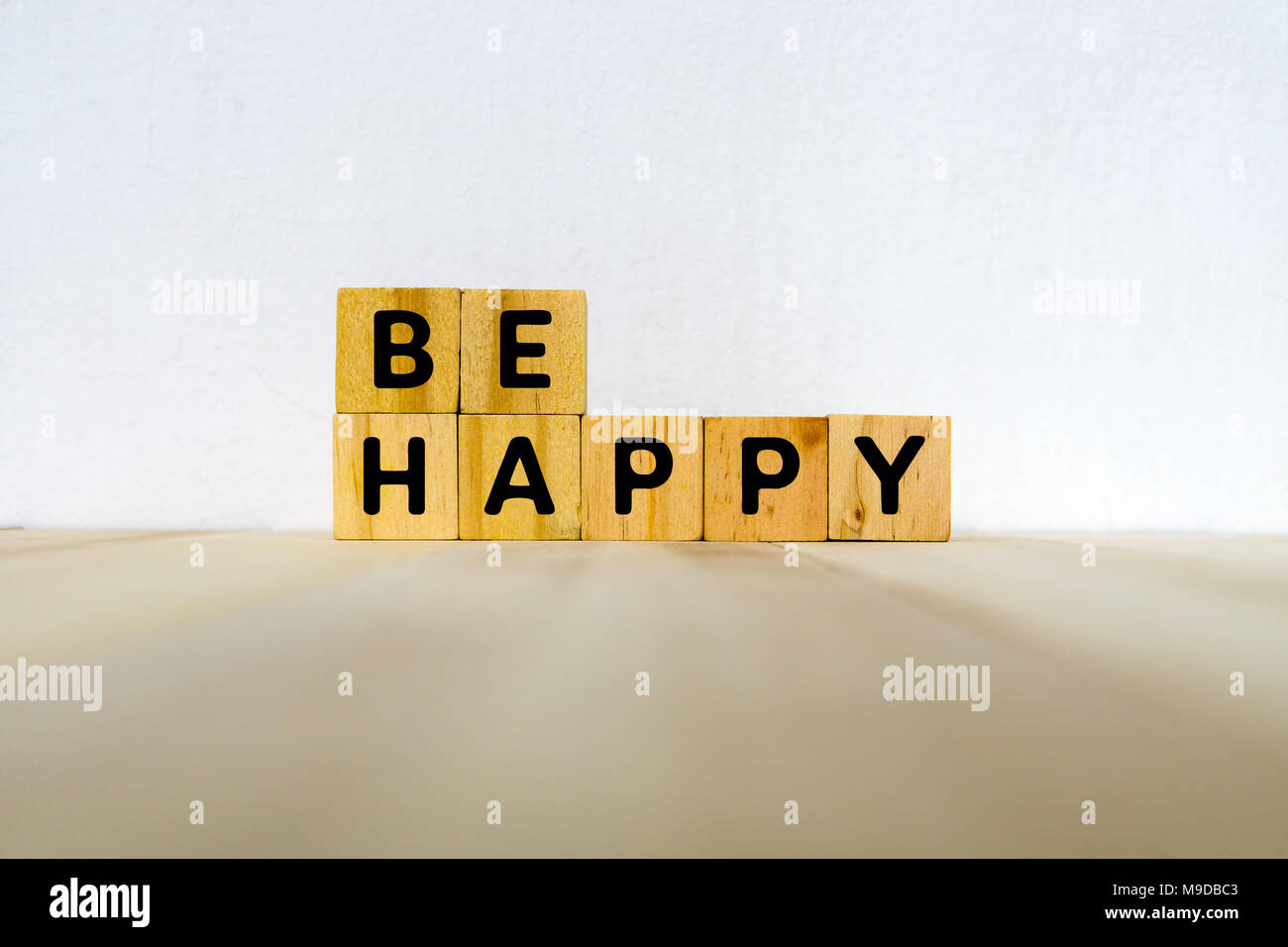 Be happy word on wood block - motivational concept - Stock Image