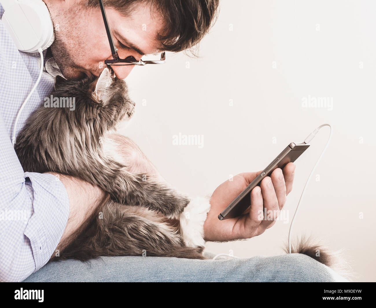 Cute man wearing glasses with headphones and a mobile phone on a white background, gently hugging a cute kitten. People, pets, care - Stock Image