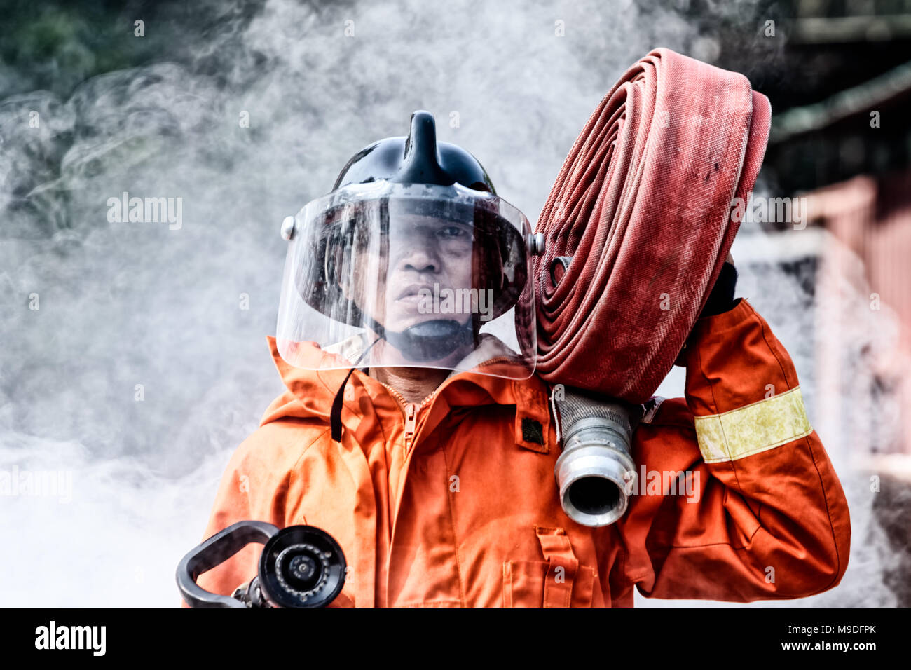 Emergency Fire Rescue training, firefighters in uniform,  carry a water hose run through flame - Stock Image