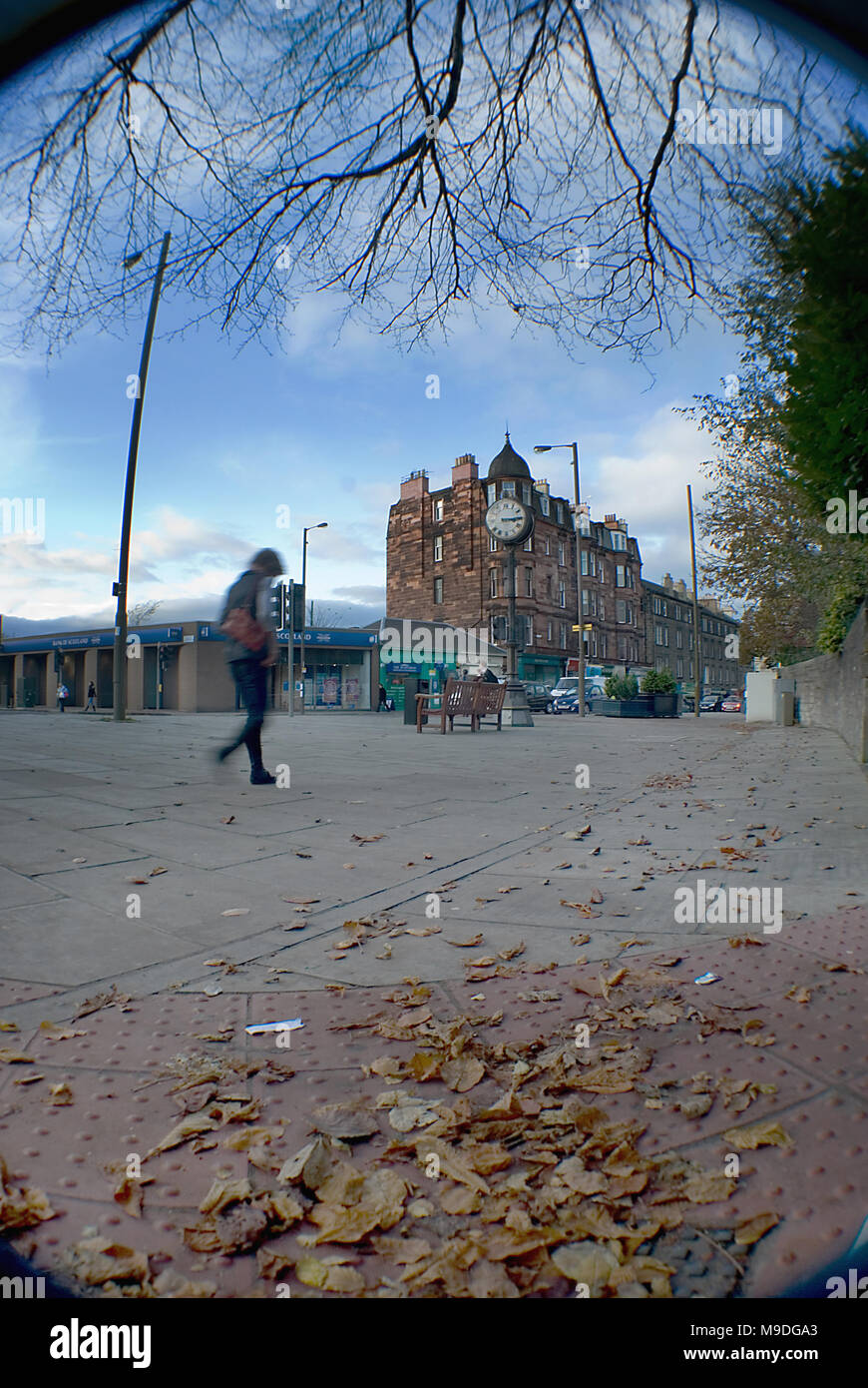 EDINBURGH, SCOTLAND - NOVEMBER 4TH 2009: A woman strolling towards the Morningside clock in Edinburgh. - Stock Image