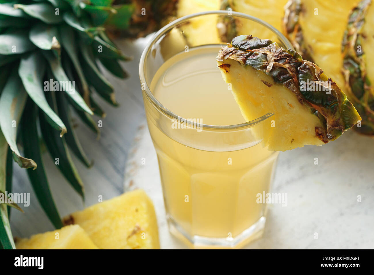 Pineapple freshly squeezed juice in glass on a wooden table over grey concrete background - Stock Image