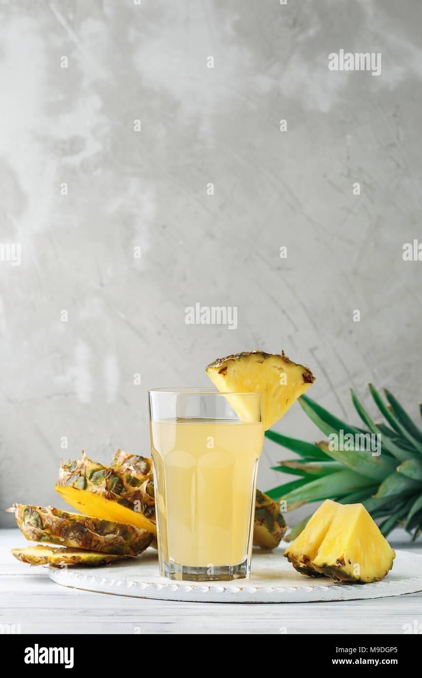 Pineapple freshly squeezed juice in glass on a wooden table over grey concrete background, front view - Stock Image