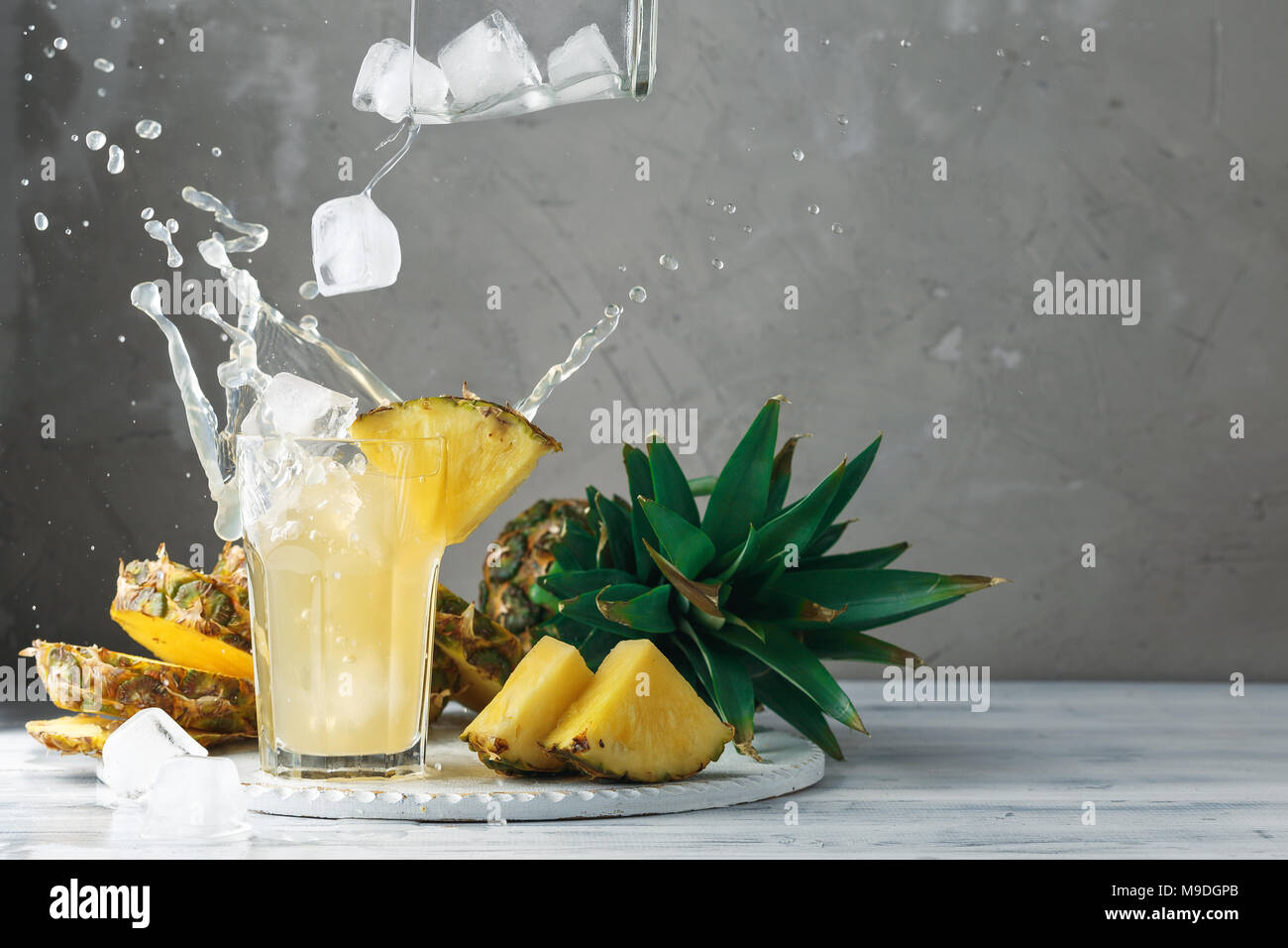 Pineapple fresh juice with falling ice cubes making splash. Cut fruit slices on wooden table and grey concrete background, front view - Stock Image