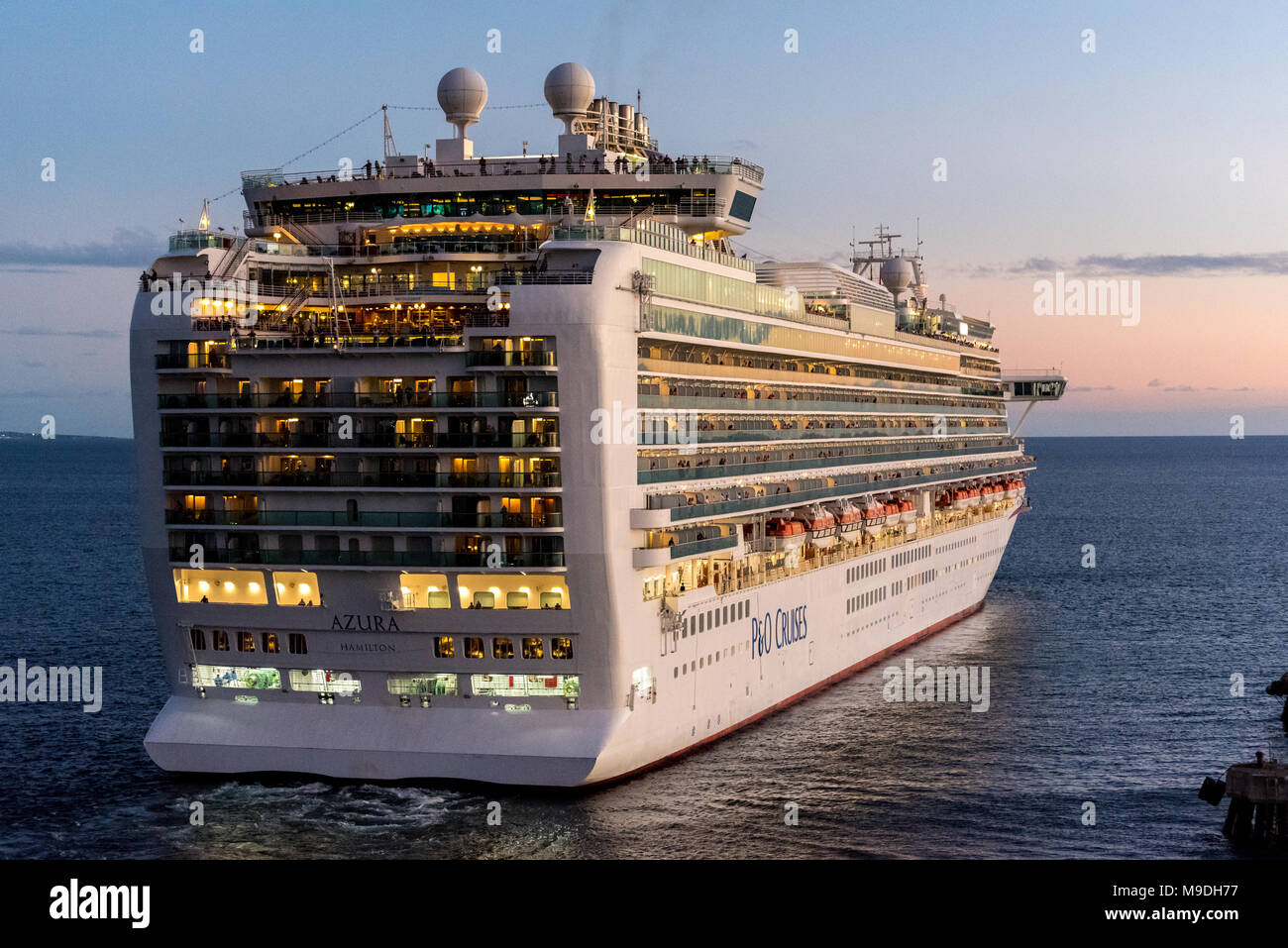 P&O Cruise Ship Azura leaving Basseterre on Saint Kitts as the sun goes down on a warm evening - Stock Image