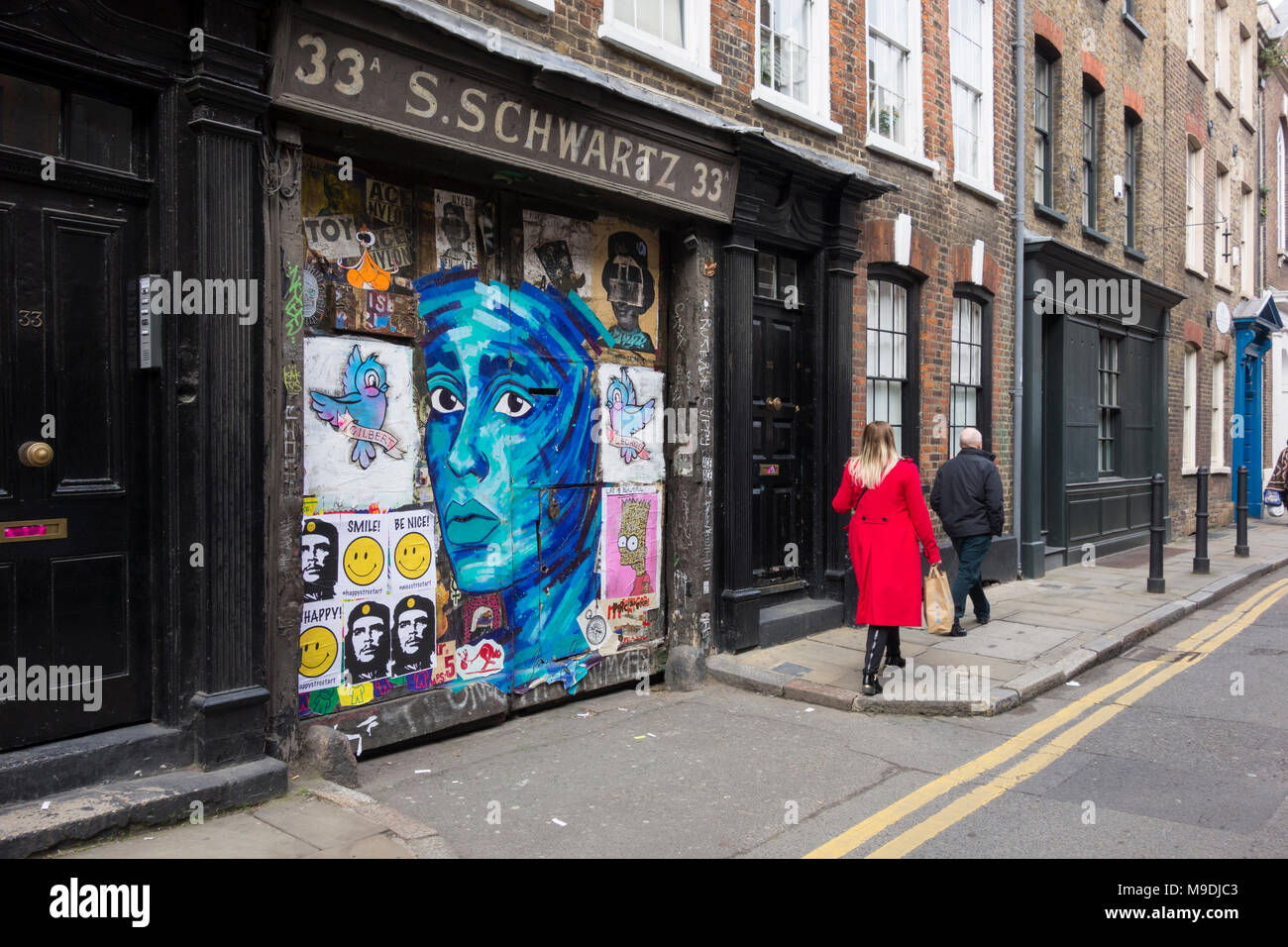 Street art on the gates to S. Schwartz at 33 Fournier Street, Spitalfields, London, E1, UK Stock Photo