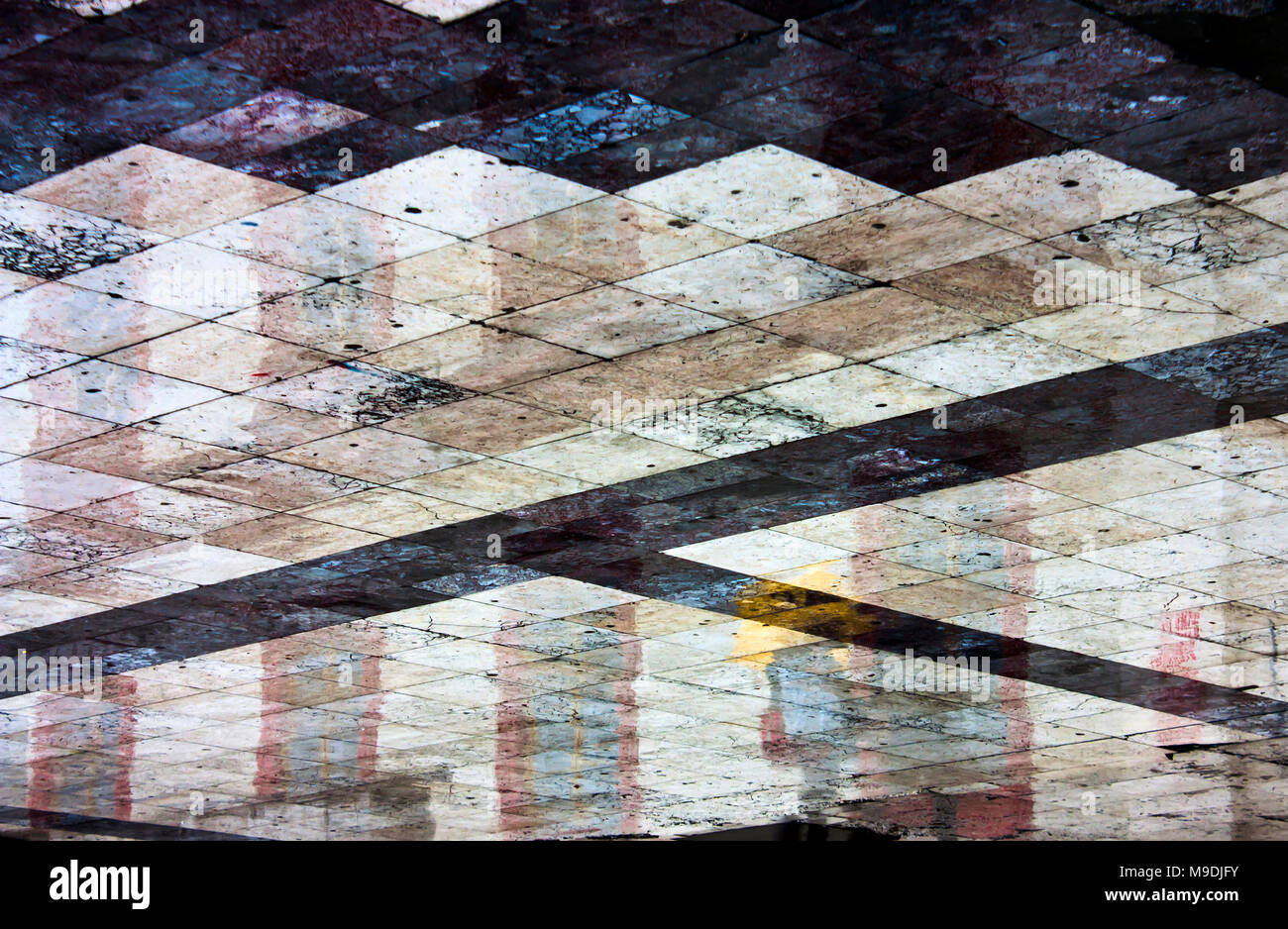 Abstract wet shiny geometrical city square pavement reflecting buildings and people on a rainy day Stock Photo