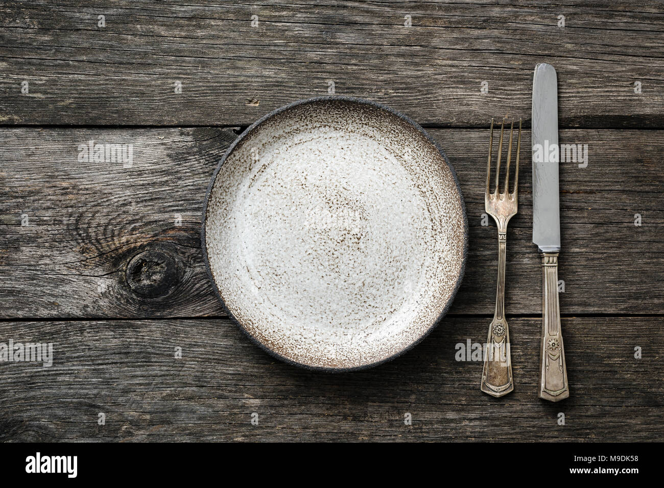 Table setting with vintage silverware or cutlery and empty plate on rustic wood. Top view with copy space for text & Table setting with vintage silverware or cutlery and empty plate on ...