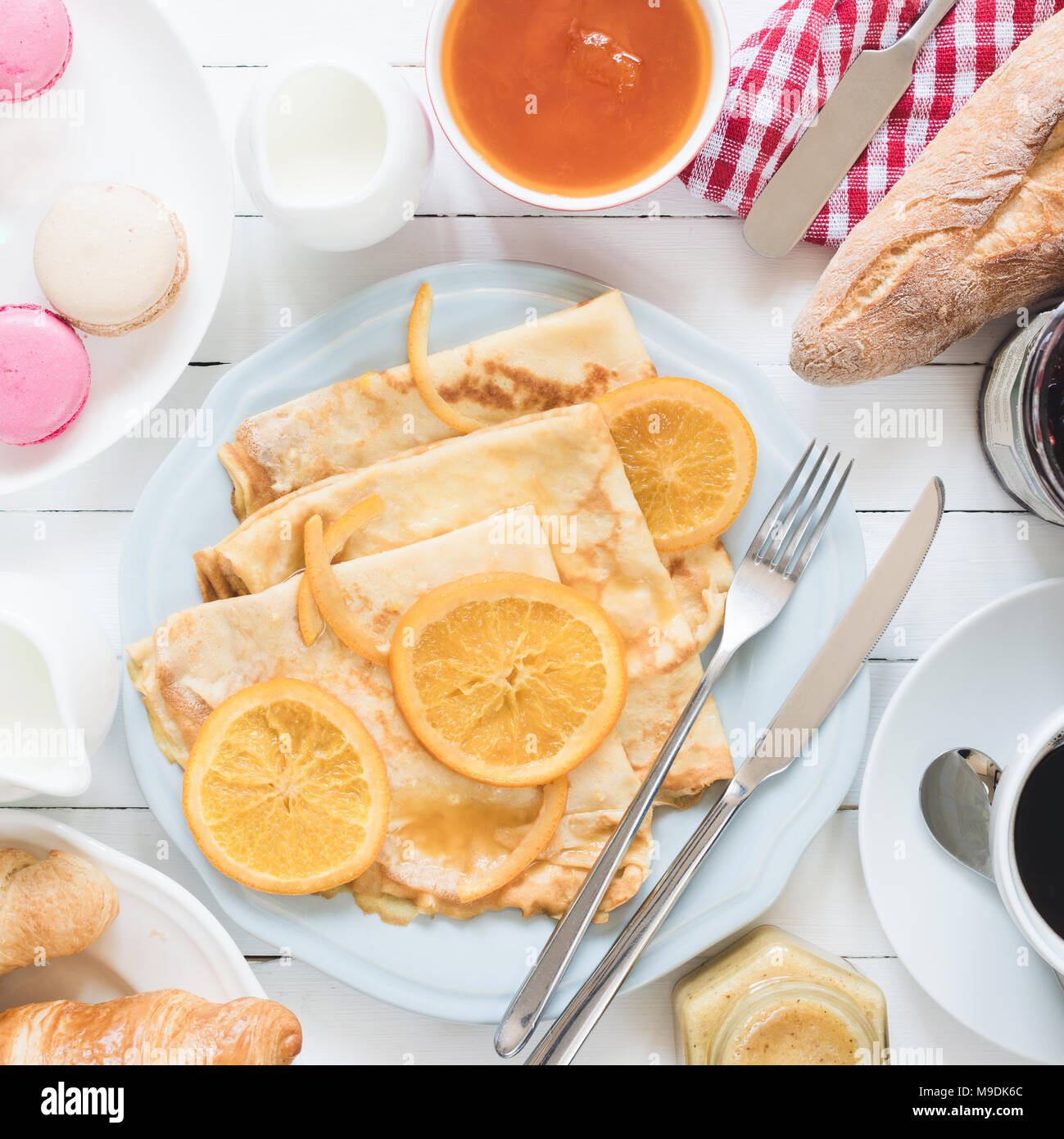 Crepes Suzette on blue plate, jam, baguette, coffee and macarons. Traditional french breakfast. Top view, square crop - Stock Image