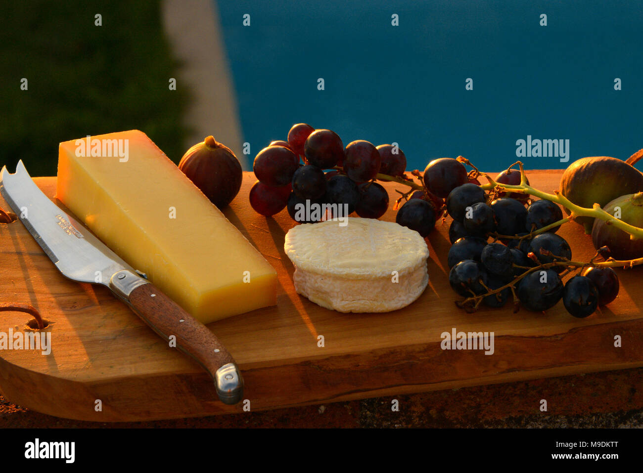 Grapes, figs and Chèvre cheese on a wooden platter at sunset, with a traditional Occitanie Laguiole knife.. - Stock Image