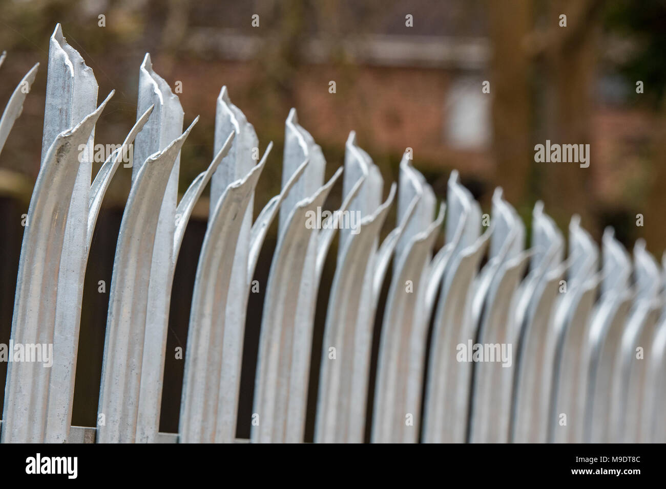 razor sharp palisade security fencing surrounding private property. security measures and fencing for protection and surrounding secure and securing. - Stock Image