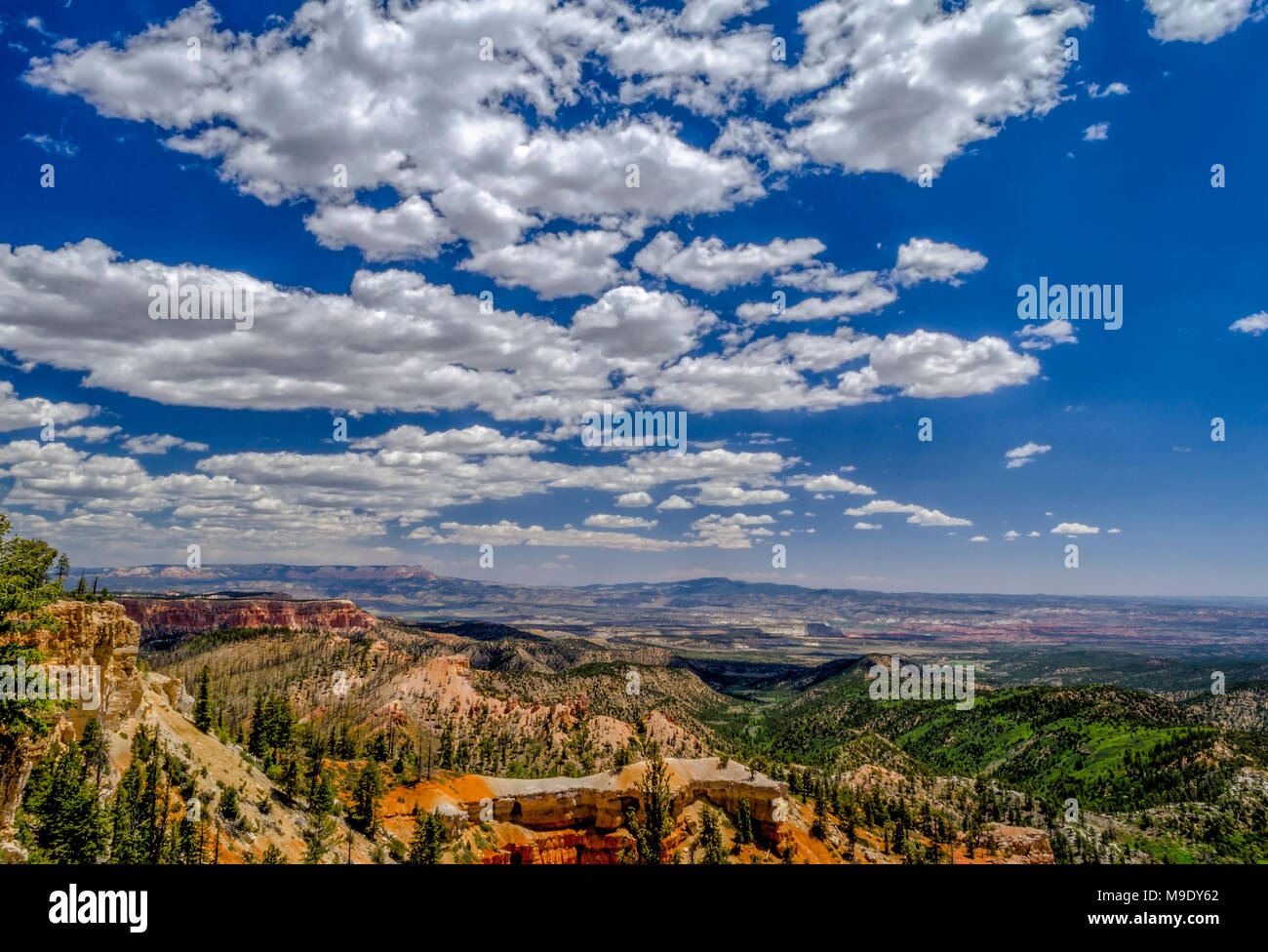 Overlooking a valley with orange and red hillsides and cliffs with green valley below under a bright blue sky with white fluffy clouds. - Stock Image