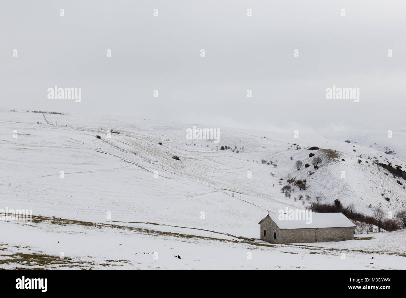 A small mountain retreat covered by snow on Mt. Subasio (Umbria, Italy) during winter season - Stock Image