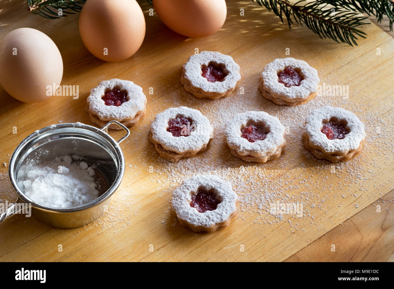 Trraditional Linzer Christmas cookies dusted with sugar, with a sifter and eggs in the background - Stock Image