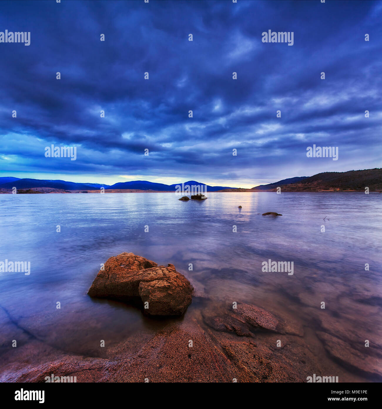 Cloudy sunrise over Jindabyne lake in NSW snowy mountains region of Australia. Clear water of mountain lake shows rocky botton and reflects sunlight. - Stock Image