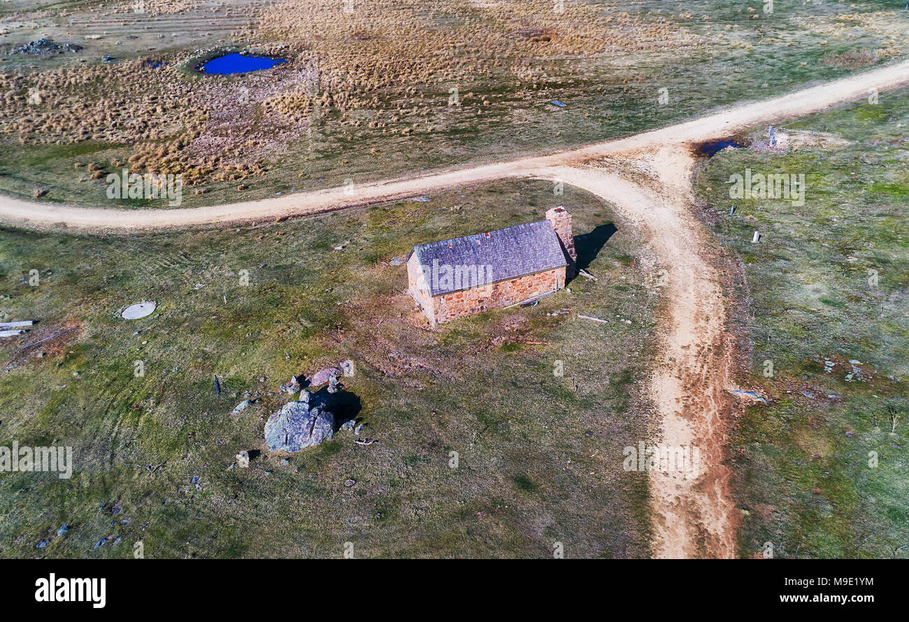 Abandoned stone farm house hut near Crackenback in Thredbo valley of Snowy mountains, Australia. Aerial view over the house and nearby unsealed road w - Stock Image