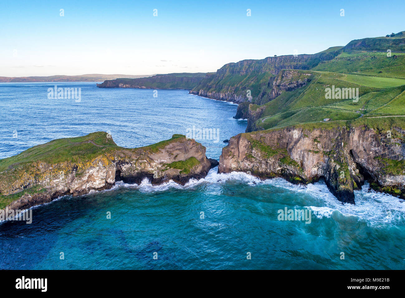 Northern Ireland, UK. Atlantic coast with cliffs and far aerial view of Carrick-a-Rede Rope Bridge in County Antrim - Stock Image