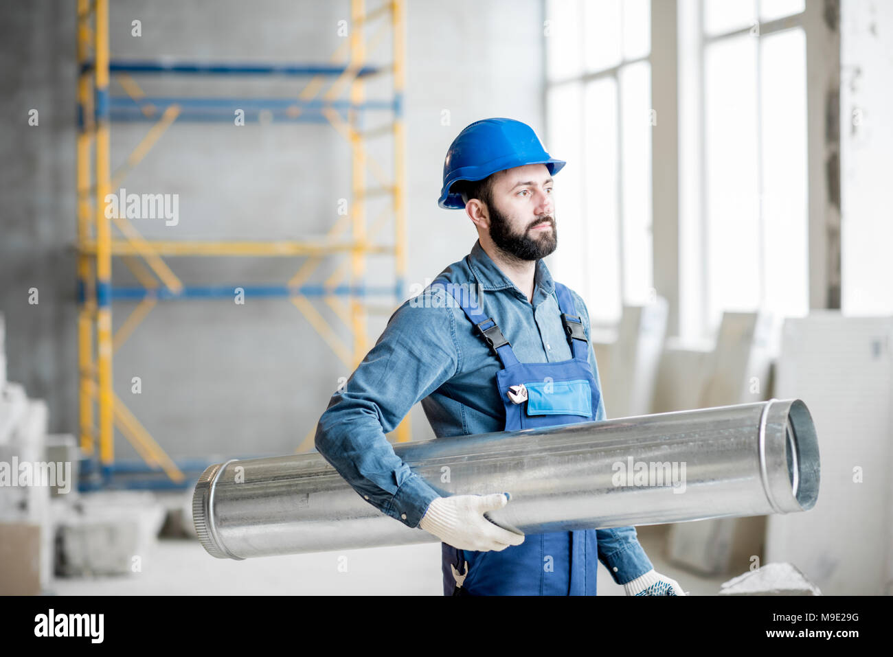 Builder with pipe indoors - Stock Image