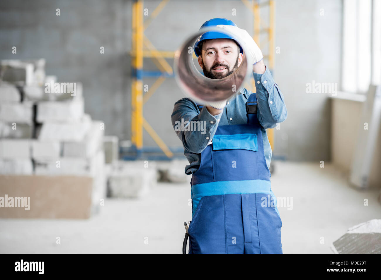 Builder with ventilation pipe - Stock Image