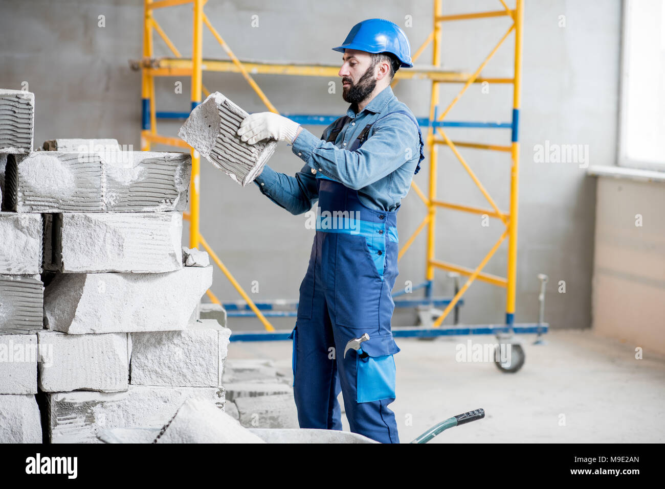 Builder working with blocks indoors - Stock Image