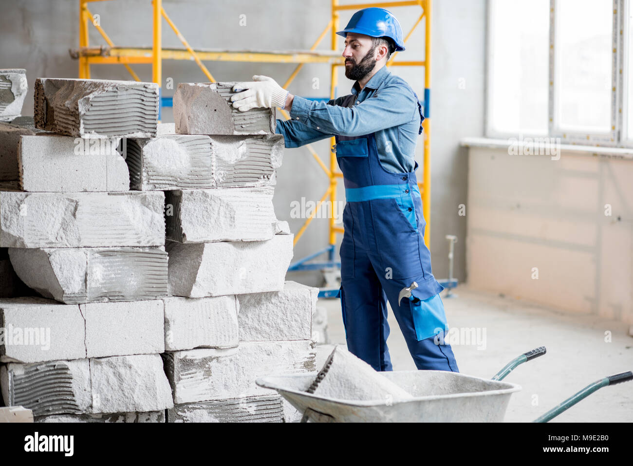 Builder working with blocks indoors - Stock Image