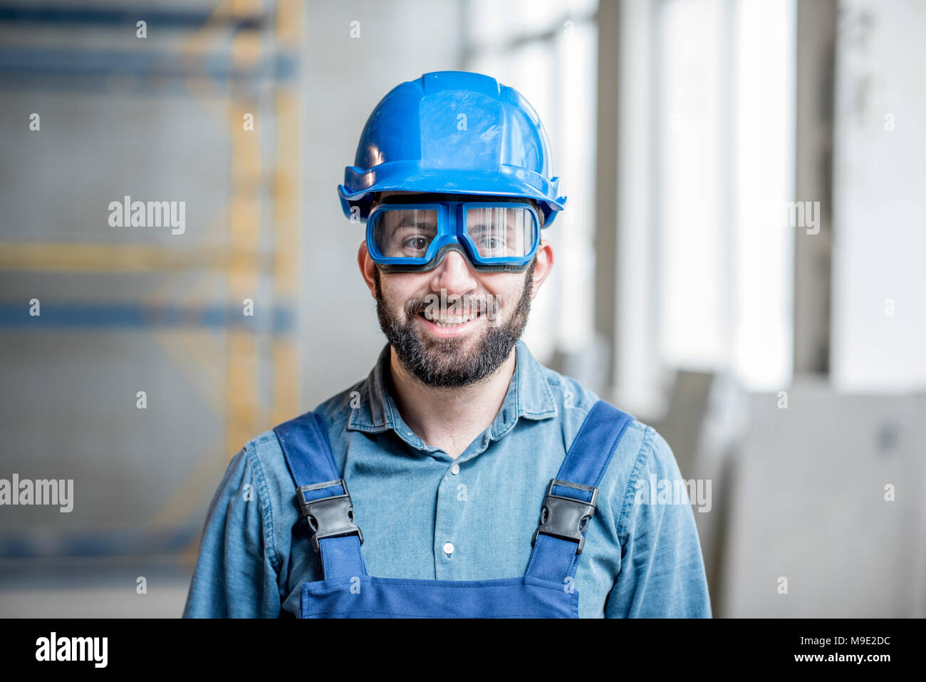 Builder in uniform indoors - Stock Image